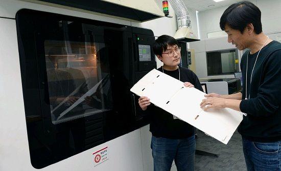 LG전자 연구원들이 창원 R&D센터에 위치한 3D프린터로 만든 냉장고 부품을 살펴보고 있다. (사진=LG전자)