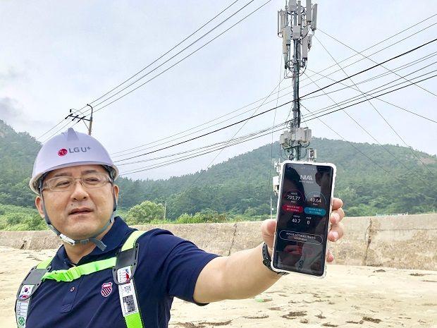 LG유플러스 직원이 전북 익산 선유도 해수욕장에서 5G 속도를 테스트한 결과를 보여주고 있다,
