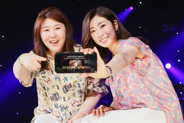 SK텔레콤은 7월 18일부터 음악공연 영상에서 본인이 선호하는 뮤지션이나 연주만 선택해 보고 들을 수 있는 새로운 방식의 5G 음악서비스 '뮤직 멀티뷰'를 모바일 OTT옥수수(Oksusu)에서 선보인다고 16일 밝혔다. 사진은 인기 인디밴드 제이레빗(J Rabbit) 가수 정다운, 정혜선이 뮤직 멀티뷰를 이용하는 모습.